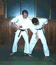 Photograph 2. Step in front of the opponent's right leg, and slap the testicles with the left hand to inflict more damage and to get the opponent to bend forward.